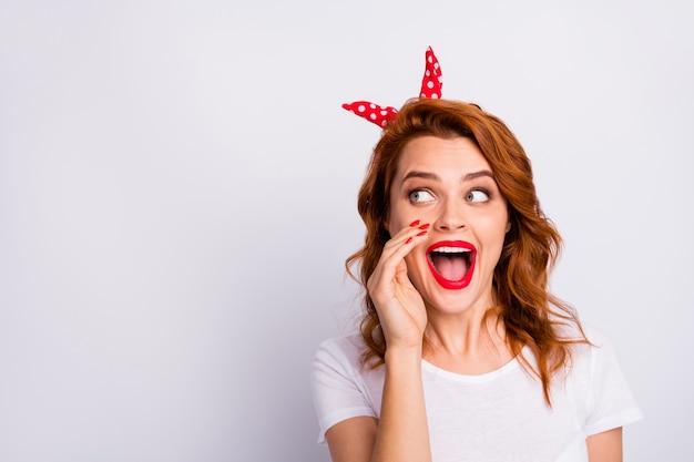 Portret szalonej podekscytowanej dziewczyny wygląda copyspace zobacz niesamowitą promocję spisku podziel się krzykiem ręka usta nosić stylowe ubrania izolowane na białej ścianie