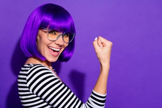 Portret szalonej zabawnej młodzieży podnoszącej pięści, krzyczącej tak na białym tle na fioletowym tle
