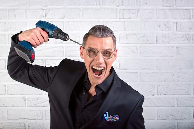 Portret szalony śmieszny młody człowiek w czarnym kostiumu ono uśmiecha się przy kamerą z świderem trzyma przy jego świątynią. strzał studio wewnętrzne. pierdolić mózg