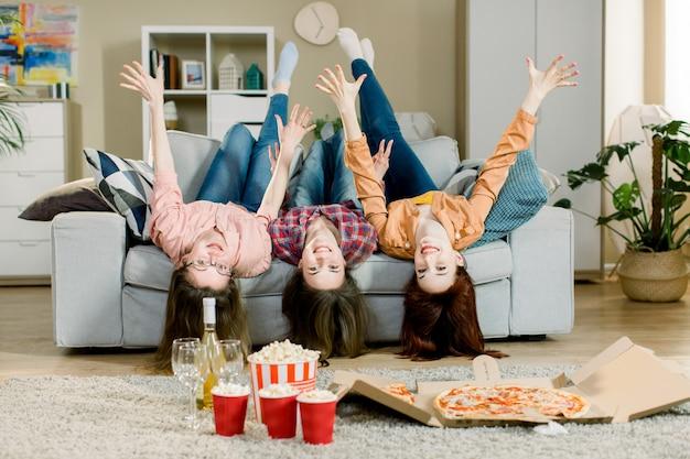 Portret szalony śmieszny trzy kobiety w przypadkowy stroju kłamać do góry nogami na kanapy mieniu wręcza w górę i patrzejący kamerę salową. domowa impreza z pizzą