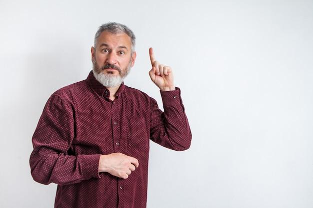 Portret szary brodaty mężczyzna ma pomysł, wskazując palcem wskazującym w górę na białym ścianie