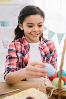 Portret szczęśliwa dziewczyna usuwa błękitnego Easter jajko od kosza na stole