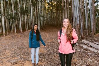 Portret szczęśliwy żeński wycieczkowicz z jej przyjacielem w lesie