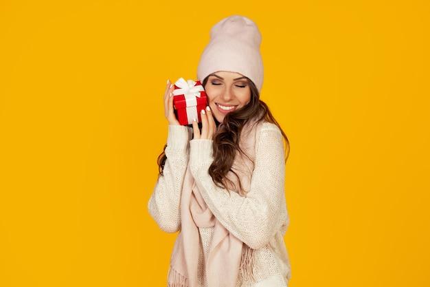 Portret szczerze zadowolonej dziewczyny, która cieszy się prezentem, który otrzymuje na boże narodzenie. kobieta trzyma czerwone pudełko