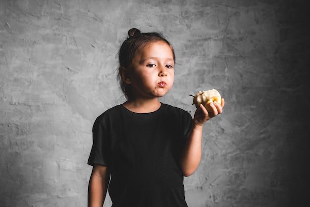 Portret szczęścia mała dziewczynka je zielone jabłko na szarym tle. zdrowie, pełnowartościowa żywność
