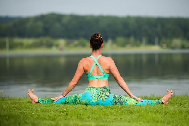 Portret szczęścia młoda kobieta praktykuje jogę na zewnątrz
