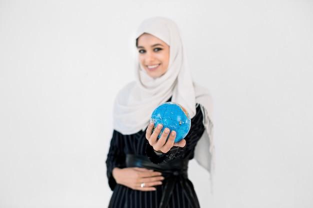 Portret szczęśliwa arabska muzułmańska kobieta trzyma światową kulę ziemską odizolowywającą na białym tle w hijab