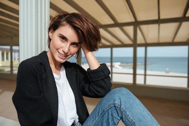 Portret szczęśliwa atrakcyjna młoda kobieta siedzi na tarasie w pobliżu morza