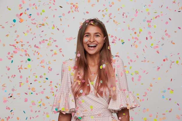 Portret szczęśliwa atrakcyjna młoda kobieta z długimi farbowanymi pastelowymi różowymi włosami nosi różową sukienkę w kropki i imprezę