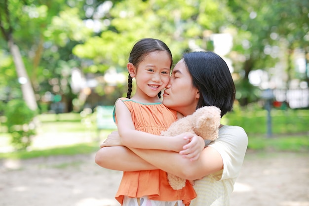 Portret szczęśliwa azjata matka przytula córki i ściska misia lalę w ogródzie.