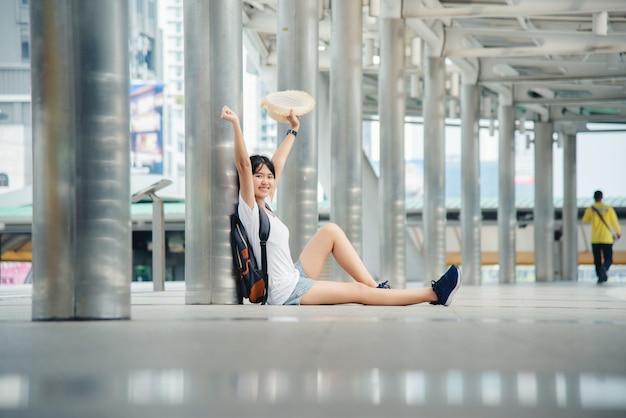 Portret szczęśliwa azjatycka młoda kobieta siedzi na mieście