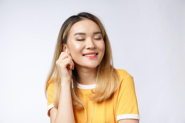 Portret szczęśliwa azjatycka młoda kobieta słucha muzyki przez słuchawki