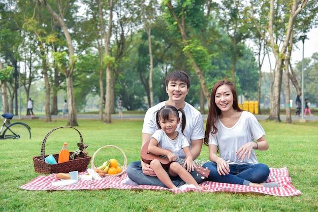 Portret szczęśliwa azjatycka rodzina w ogródzie