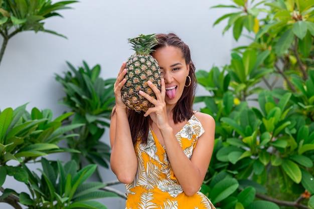 Portret szczęśliwa azjatykcia uśmiechnięta kobieta w żółtej letniej sukience trzymaj ananas