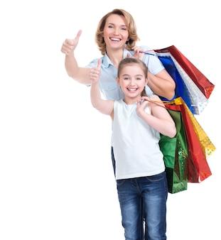 Portret szczęśliwa biała matka i córka z torby na zakupy pokazuje kciuki do góry - na białym tle
