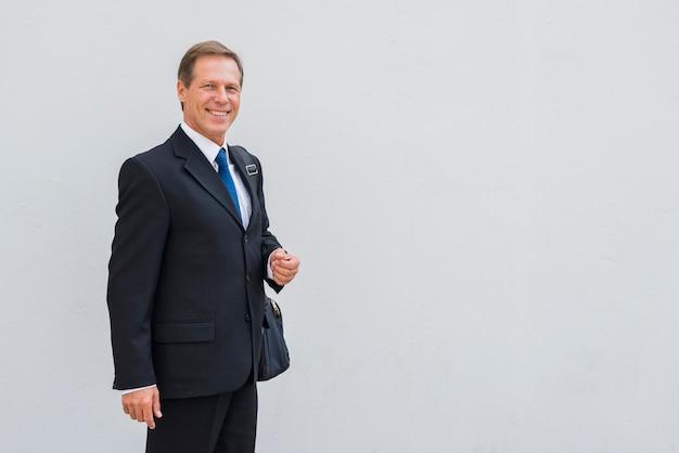 Portret szczęśliwa biznesmen pozycja przeciw popielatemu tłu