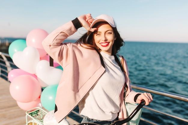Portret szczęśliwa brunetka dziewczyna ubrana w różowe ubrania przychodzące do morza po porannej przejażdżce rowerem po mieście.