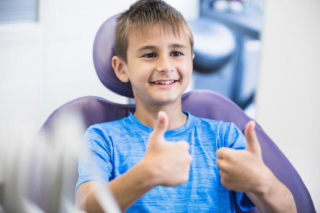 Portret szczęśliwa chłopiec gestykuluje aprobaty w klinice