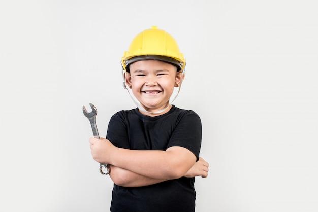 Portret szczęśliwa chłopiec jest ubranym inżyniera kapelusz
