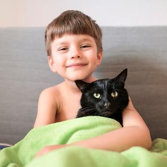 Portret szczęśliwa chłopiec z jego kotem