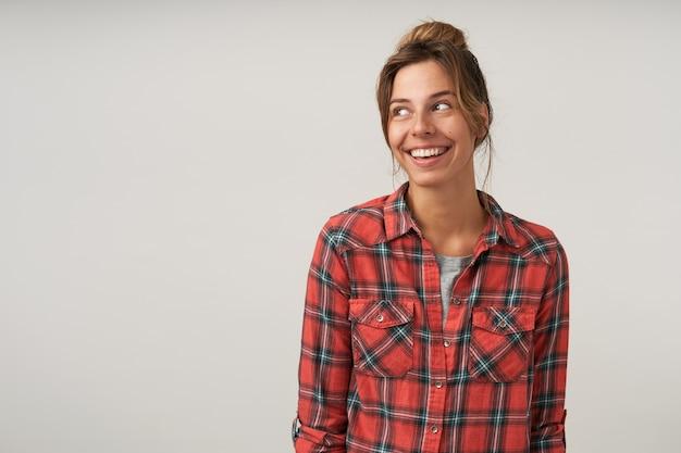 Portret szczęśliwa ciemnowłosa młoda kobieta z fryzurą kok, pozowanie na białym tle, ubrana w ubranie, patrząc na bok z radosnym uśmiechem