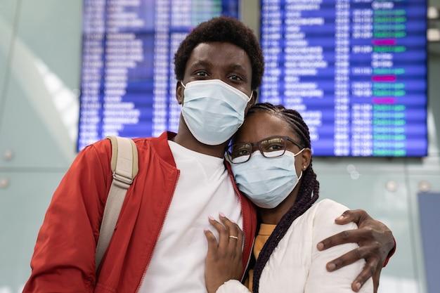 Portret szczęśliwa czarna para podróżnych w maskach medycznych na tablicy terminala lotniska