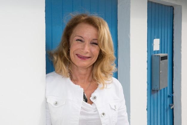 Portret szczęśliwa dojrzała kobieta na błękitnym tle
