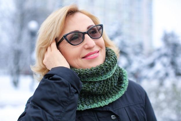 Portret szczęśliwa dojrzała kobieta w śnieżnym parku na ferie zimowe