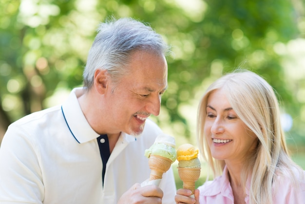 Portret szczęśliwa dojrzała para je lody w parku