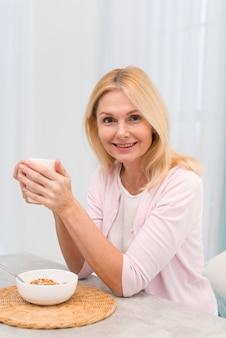 Portret szczęśliwa dorosła kobieta trzyma filiżankę