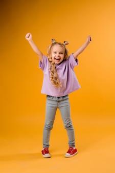 Portret szczęśliwa dziecko dziewczyna odizolowywa na żółtej przestrzeni, przestrzeń dla teksta