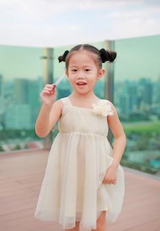 Portret szczęśliwa dziecko dziewczyna w sukni przy dachem budynek