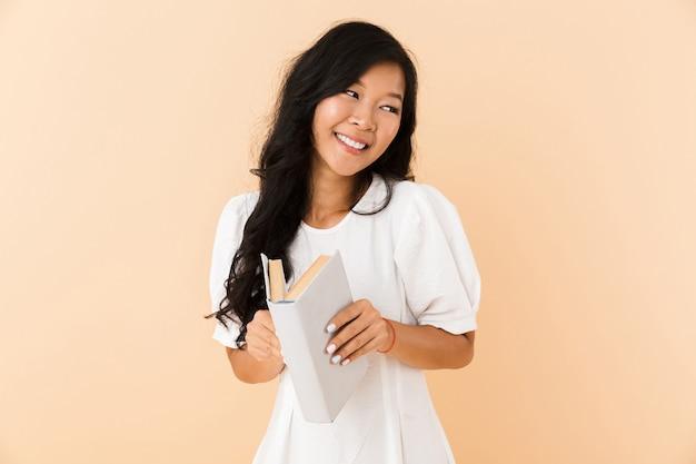 Portret szczęśliwa dziewczyna azjatyckich na białym tle nad beżem