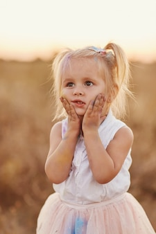 Portret szczęśliwa dziewczyna mażąca kolorowym proszkiem. mała dziewczynka z dwoma ogonami