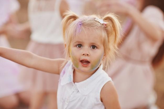 Portret szczęśliwa dziewczyna rozmazana kolorowym proszkiem. mała dziewczynka z dwoma ogonami
