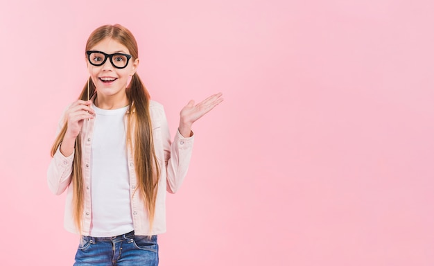 Portret szczęśliwa dziewczyna trzyma eyeglasses podpiera wzruszać ramionami przeciw różowemu tłu