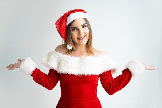 Portret szczęśliwa dziewczyna wzrusza ramionami ramiona w święty mikołaj stroju