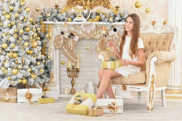 Portret szczęśliwa dziewczyna z prezentami na boże narodzenie pozuje w domu