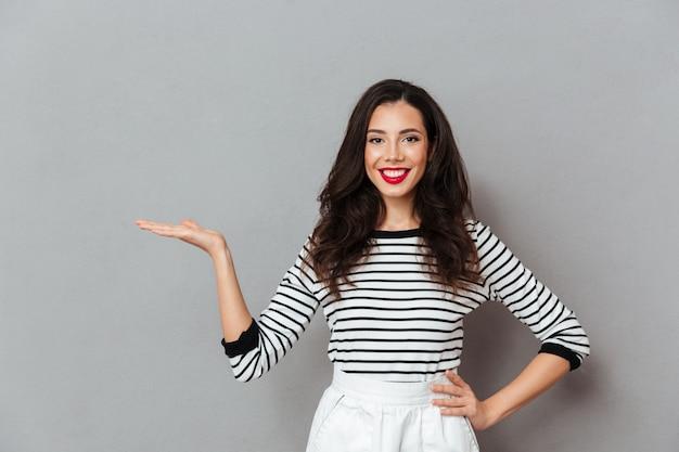 Portret szczęśliwa dziewczyny pozycja z ręką na biodrach