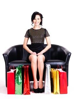 Portret szczęśliwa elegancka kobieta w czarnej sukni z torby na zakupy siedzi na kanapie na białym tle.