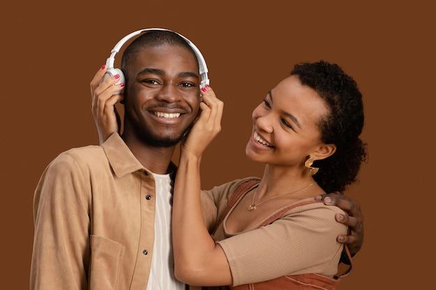 Portret szczęśliwa i uśmiechnięta para ze słuchawkami