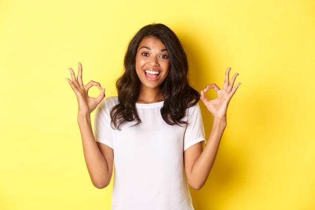 Portret szczęśliwa i zadowolona afrykańska dziewczyna ubrana w białą koszulkę pokazującą dobre znaki