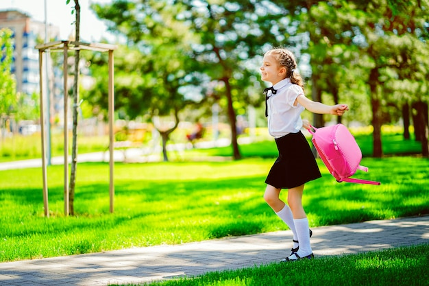 Portret szczęśliwa kaukaska młoda uśmiechnięta dziewczyna jest ubranym szkolnego plecaka poza szkołę podstawową.