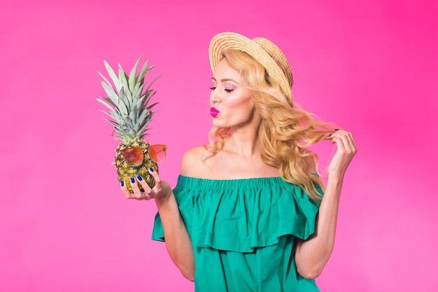 Portret szczęśliwa kobieta i ananas na różowym tle. lato, dieta i zdrowy tryb życia