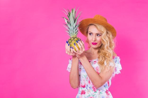 Portret szczęśliwa kobieta i ananas na różowym tle z copyspace. lato, dieta i zdrowie