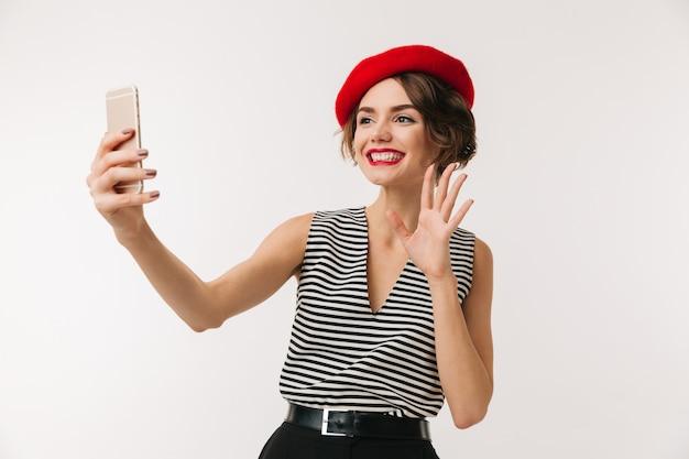 Portret szczęśliwa kobieta jest ubranym czerwonego beret