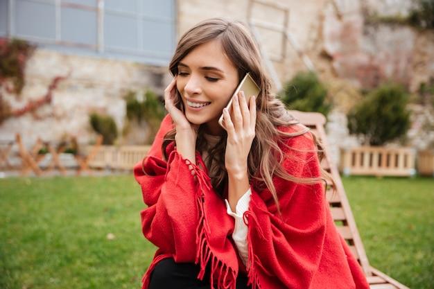Portret szczęśliwa kobieta opowiada na telefonie komórkowym