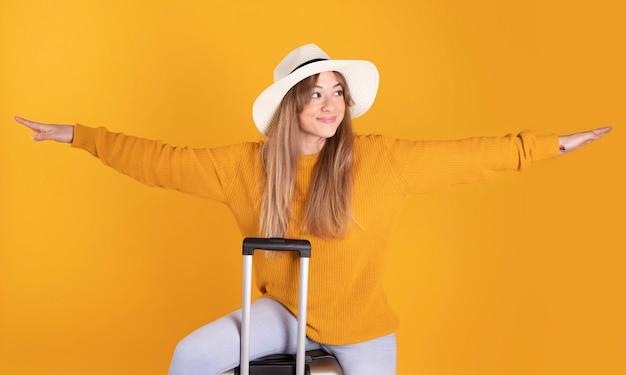 Portret szczęśliwa kobieta, podróżnik z paszportem i walizka, na kolor żółty przestrzeni