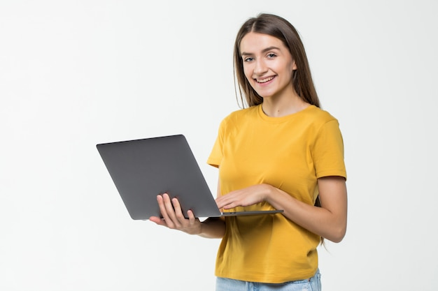 Portret szczęśliwa kobieta pracuje na laptopie odizolowywającym nad biel ścianą