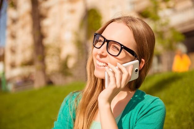 Portret szczęśliwa kobieta rozmawia przez telefon w parku w okularach